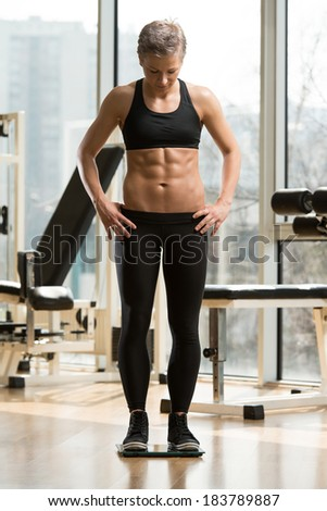 Fitness And Weight Loss - Young Woman On The Weighing Machine - stock photo