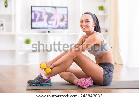 Fitness at home concept. Smiling young woman is sitting on mat with sports equipment at home. - stock photo