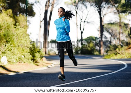 Fitness athlete training alone on a mountain road. Running endurance marathon woman exercising for healthy lifestyle and wellness. - stock photo