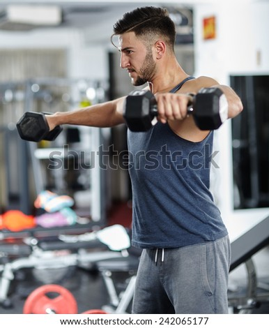 Fitness athletic sportsman doing shoulder workout with dumbbells in a gym - stock photo