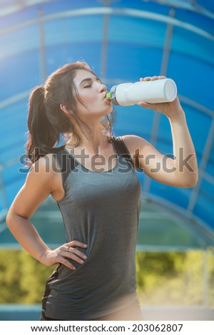 Fitness beautiful woman drinking water and sweating after exercising on summer hot day in city. Female athlete after work out. - stock photo