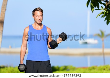 Fitness bicep curl - weight training man outdoors working out arms lifting dumbbells doing biceps curls. Male sports model exercising outside as part of healthy lifestyle. - stock photo