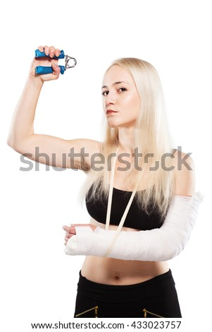 Fitness blond girl with a broken arm in plaster exercising - stock photo