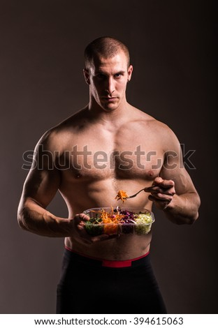Fitness bodybuilder man holding a plastic bowl and eating fresh salad, isolated on dark background - stock photo