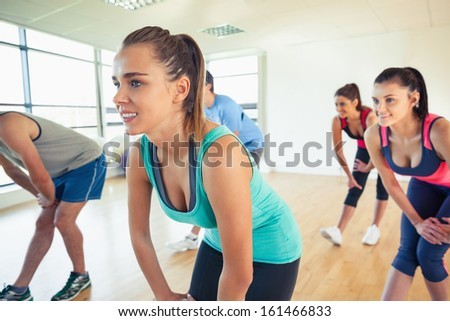 Fitness class and instructor doing power fitness exercise in fitness studio - stock photo