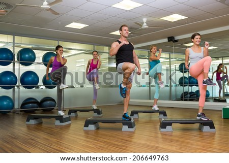 Fitness class doing step aerobics at the gym - stock photo