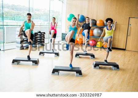 Fitness class exercising in the studio the gym - stock photo