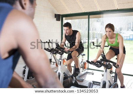 Fitness coach and two friends at a exercise bike class - stock photo