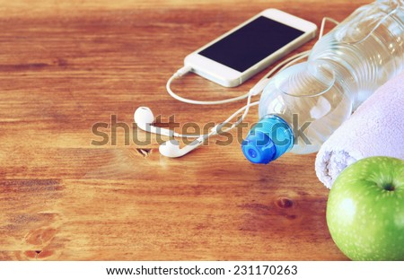 fitness concept with bottle of water, mobile phone with earphones, towel and apple over wooden background. filtered image with selective focus - stock photo