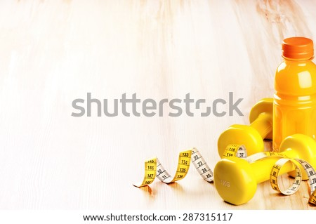 Fitness concept with dumbbells and fresh fruit juice in yellow tone  - stock photo