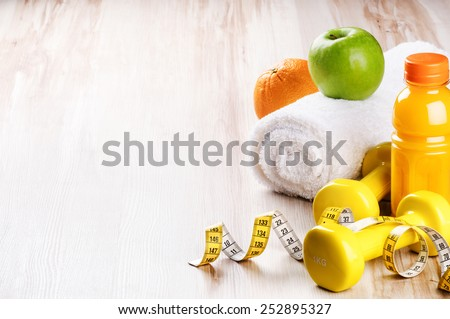 Fitness concept with dumbbells and fresh fruits  - stock photo