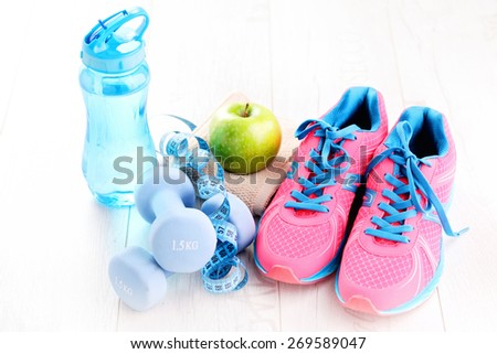 fitness concept with dumbbells and green apple - sport and leisure - stock photo