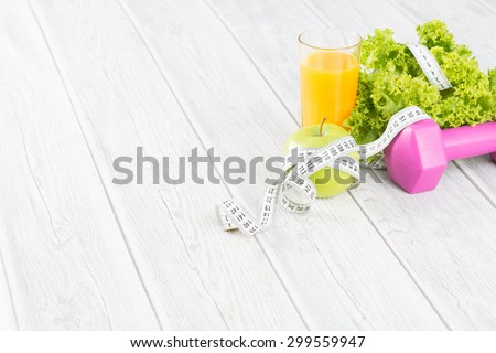 Fitness concept with dumbbells and healthy food. - stock photo