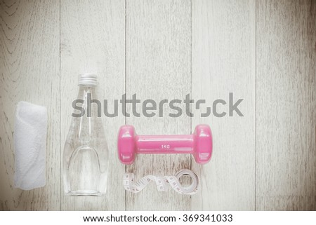 Fitness concept with dumbbells and water bottle, Vintage Style. - stock photo