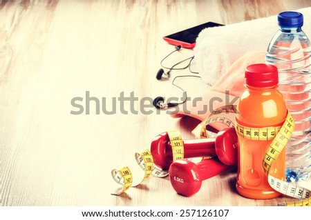 Fitness concept with dumbbells, fruits juice, water bottle and sportswear - stock photo
