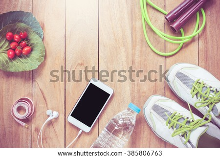 fitness concept with Exercise Equipment ,jump rope,shoes,smartphone,Measure A,on wooden table. - stock photo