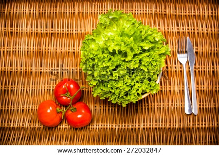 Fitness concept with healthy dieting and healthy lifestyle.Concept of diet,health and nutrition.Vibrant colorful vegetables on table.Eating salad.Bright red tomatoes and lettuce diet meal - stock photo