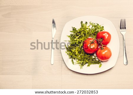 Fitness concept with healthy dieting and healthy lifestyle.Concept of diet,health and nutrition.Vibrant colorful vegetables on plate.Eating salad.Bright red tomatoes and rucola diet meal - stock photo