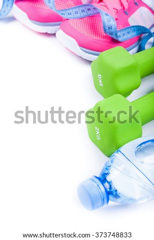 Fitness concept with sporty footwear, dumbbells and mineral water on white, free space for your text - stock photo
