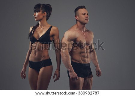 Fitness couple. Athletic woman in a black lingerie and shirtless bodybuilder isolated on a grey background. - stock photo