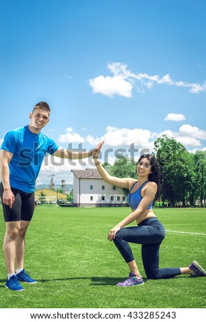 Fitness couple giving high five motivation gesture. Outdoor fitness open grass field. - stock photo