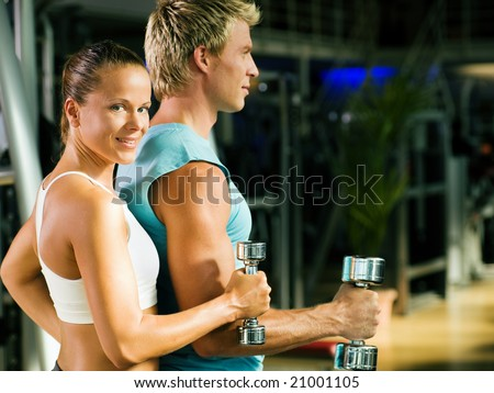 Fitness couple in the gym, rivaling each other, exercising with weights (focus on the face of the girl) - stock photo