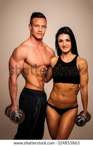 Fitness couple poses in studio - fit man and woman - stock photo