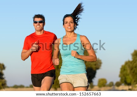 Fitness couple running in country road. Cheerful runners training outdoors on summer for sport and healthy lifestyle. - stock photo