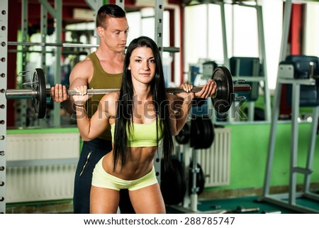 Fitness couple workout - fit mann and woman train in gym - stock photo