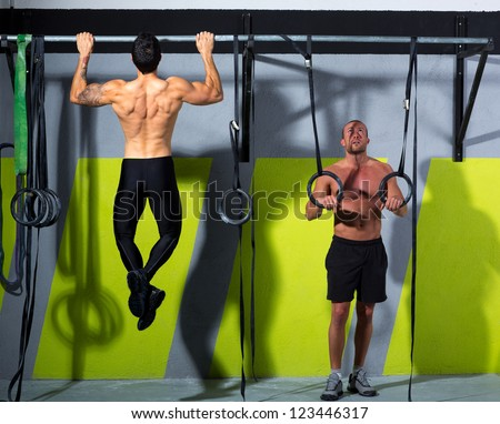 Fitness dip ring and toes to bar man pull-ups men workout at gym - stock photo