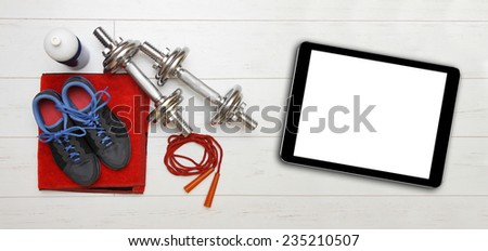fitness equipment and blank digital tablet on gym floor - stock photo