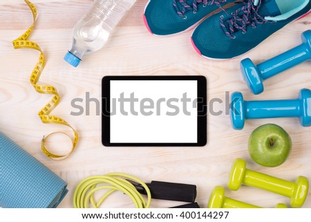 Fitness equipment and blank tablet on wooden background  - stock photo
