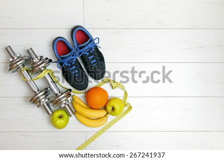 fitness equipment and fruits on white wooden plank floor - stock photo