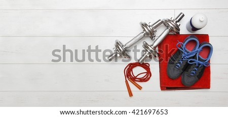 fitness equipment on white wooden plank floor with copy space - stock photo