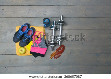 fitness equipment with copy space on gray wooden plank floor - stock photo