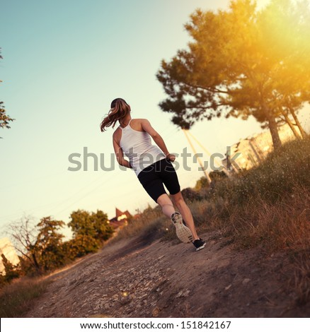 Fitness female runner working out on the nature. Sport woman jogger training outdoors for marathon run.  - stock photo