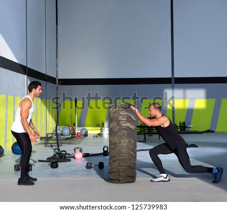 Fitness flip tires men flipping each other the wheel workout - stock photo