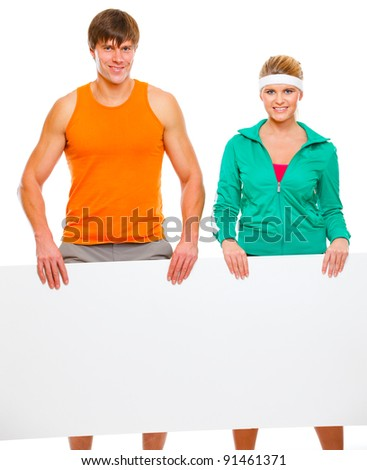Fitness girl and male athlete with blank billboard isolated on white - stock photo