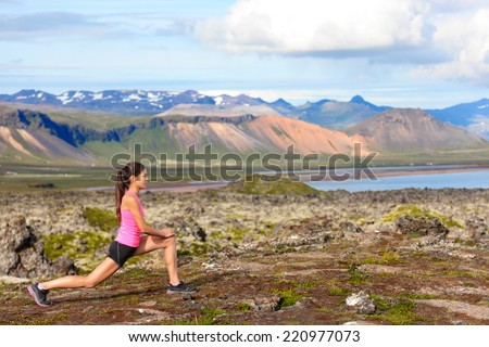 Fitness girl doing lunges exercise in nature. Female sport model exercising doing front forward lunge training legs and glute outside in beautiful landscape on Iceland. - stock photo