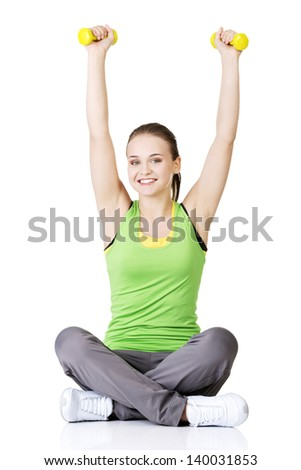 Fitness girl is working out with dumbbells , isolated on white background - stock photo