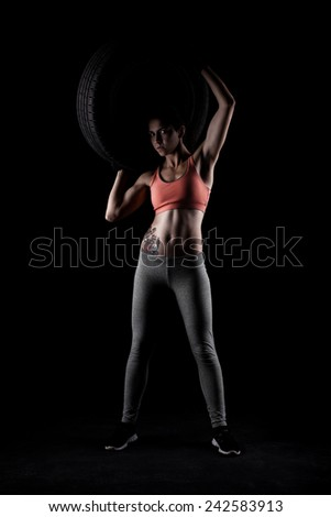 fitness girl lifting a tyre, against black background - stock photo