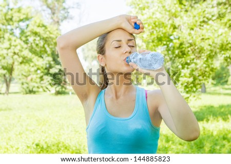 Fitness girl refreshment drinking water in the park. - stock photo