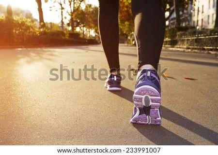 Fitness Girl running at sunset in city center - stock photo