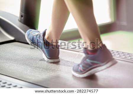 Fitness girl running on treadmill. Woman with muscular legs in modern gym - stock photo