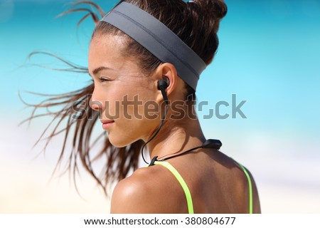 Fitness girl with sport in-ear wireless headphones. Asian female athlete woman runner wearing Bluetooth earphones with wing tip design for sports activities. Portrait closeup. - stock photo