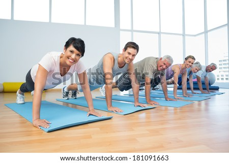 Fitness group doing push ups in row at the yoga class - stock photo