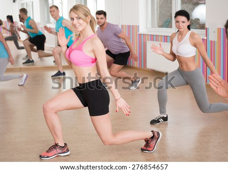 Fitness group doing squats at the gym - stock photo