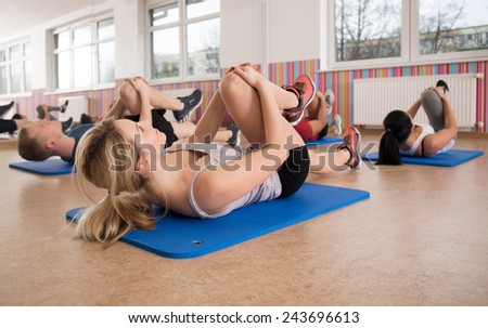 Fitness group during workout on exercise floor mats - stock photo