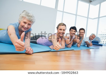 Fitness group gesturing thumbs up in row at the yoga class - stock photo