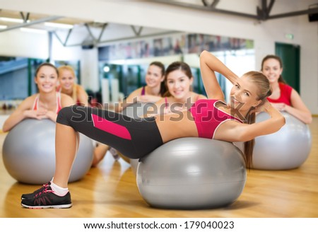 fitness, gym, exercise and health concept - young female instructor doing exercise on fitness ball infront group of people - stock photo